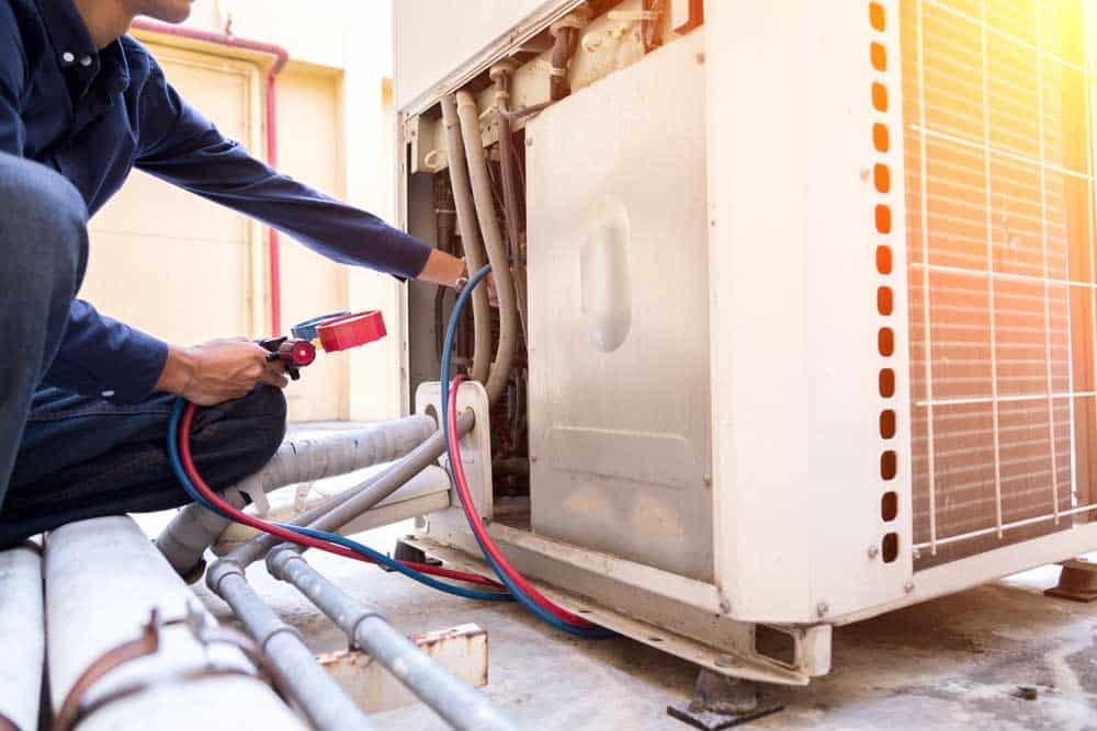 man repairing a refrigerator